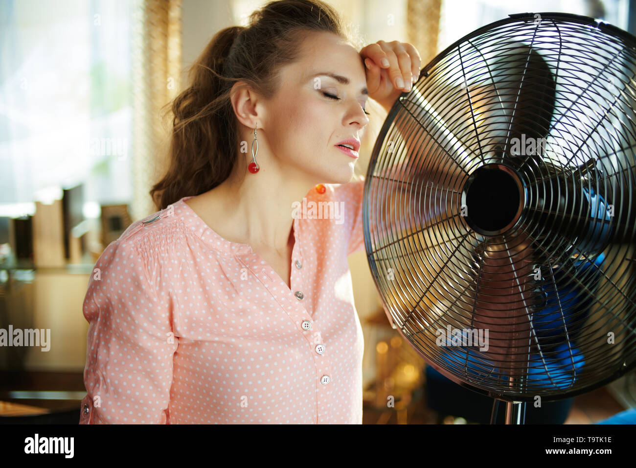 relaxed modern housewife in the modern house in sunny hot summer day enjoying fresh air in the front of working fan suffering from summer heat. - Stock Image