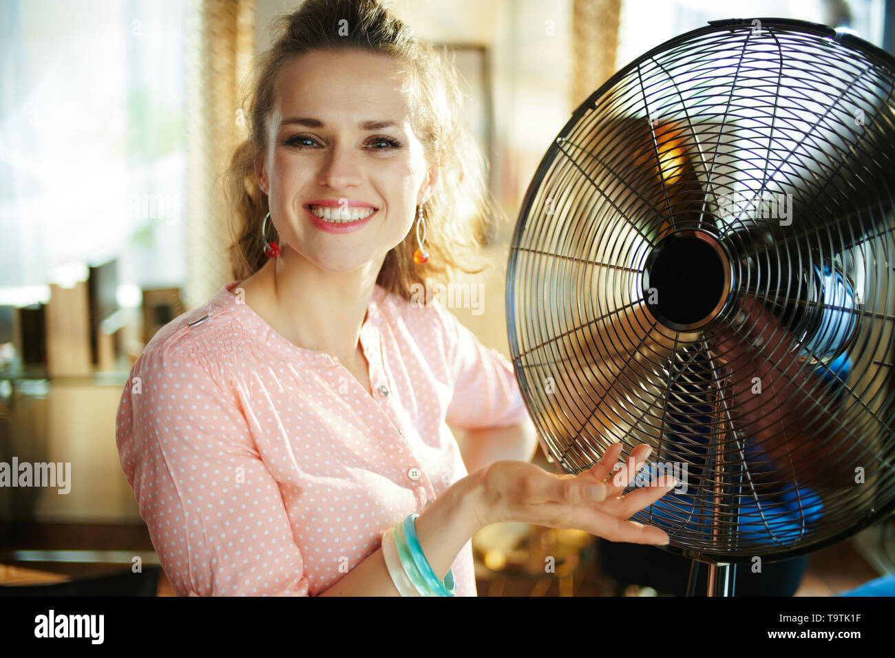 happy young housewife in the modern house in sunny hot summer day showing metallic floor standing fan. - Stock Image