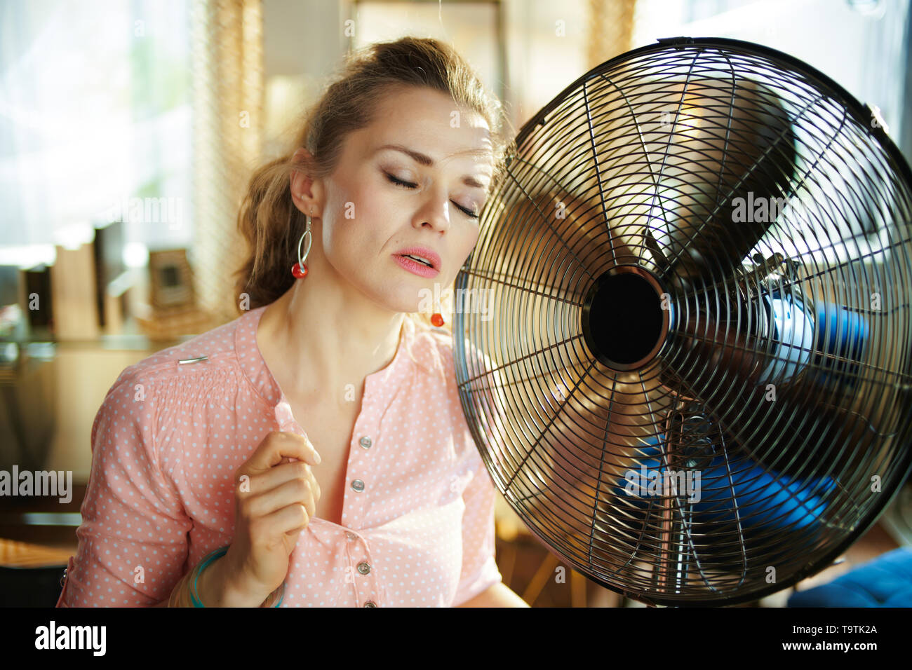sad young woman in the modern living room in sunny hot summer day enjoying breeze in the front of working fan suffering from summer heat. - Stock Image