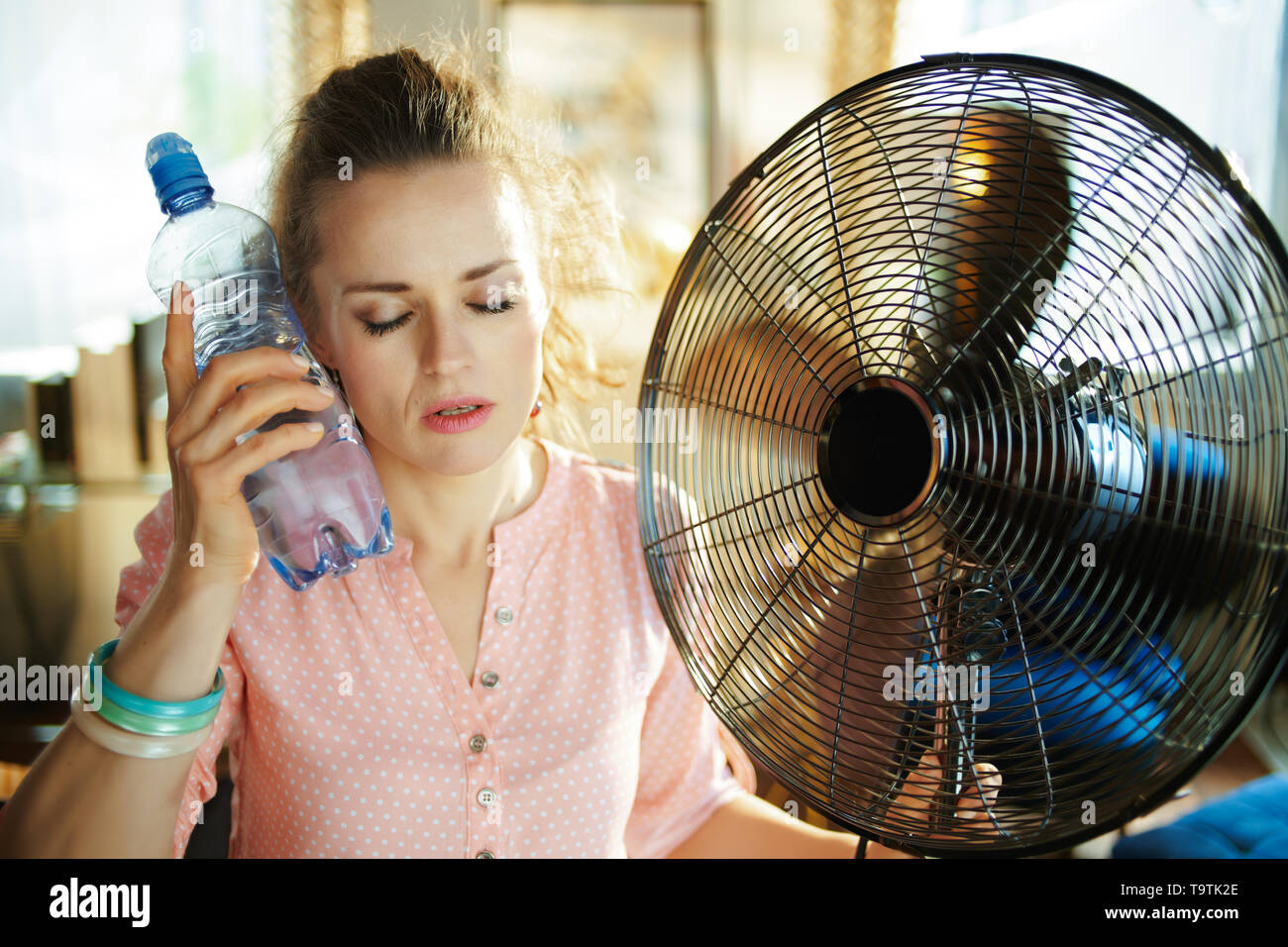 relaxed modern woman with cold bottle of water enjoying breeze in the front of working fan in the modern living room in sunny hot summer day. - Stock Image