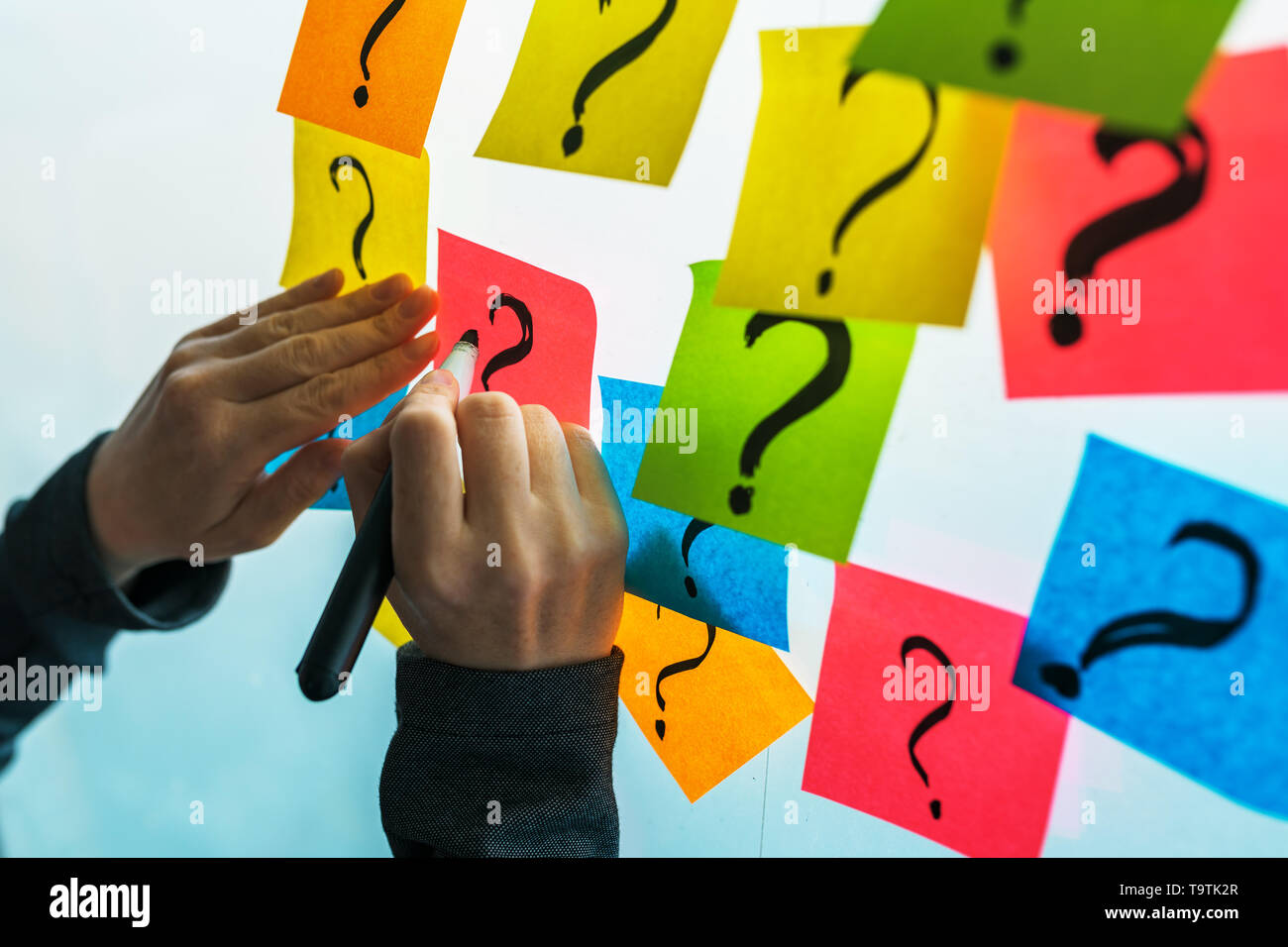 Businesswoman writing question marks on colorful sticky note paper on office whiteboard, selective focus - Stock Image