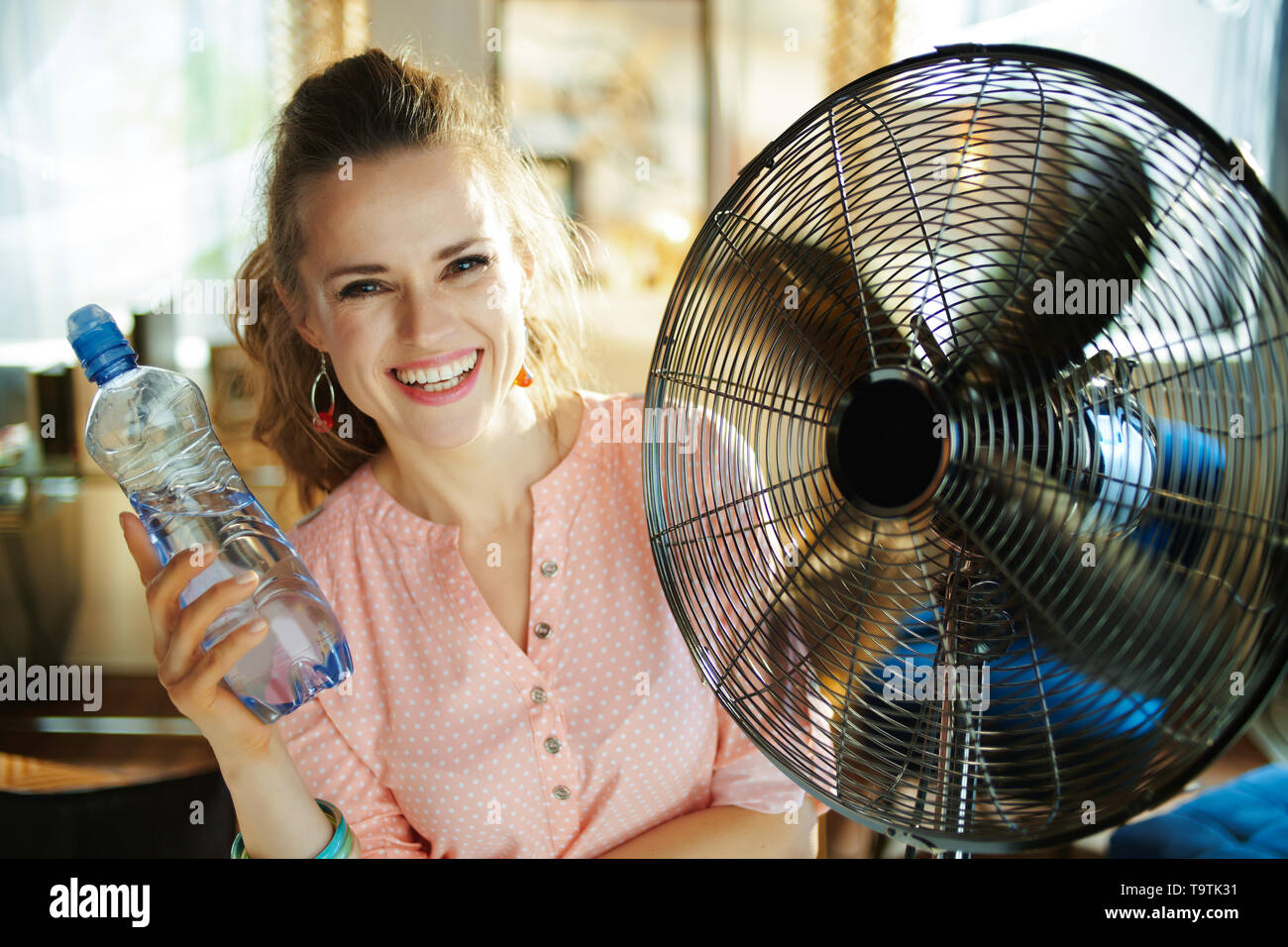 happy modern woman in the modern living room in sunny hot summer day showing cold bottle of water and enjoying fresh air in the front of working fan. - Stock Image