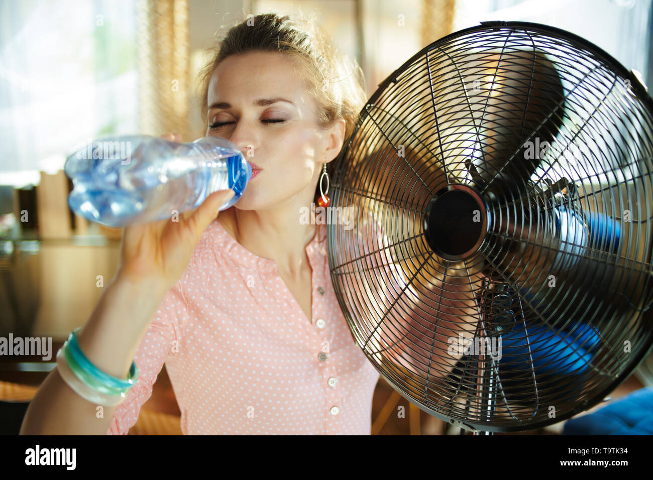 elegant woman in the modern living room in sunny hot summer day enjoying breeze in the front of working fan and drinking cold water. - Stock Image