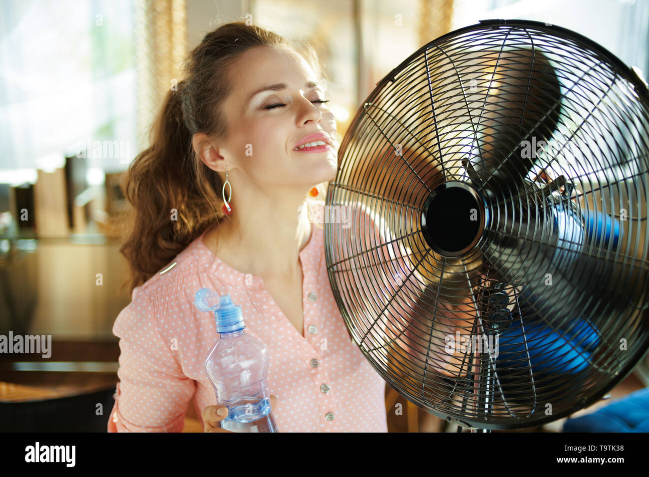 relaxed stylish housewife with cold bottle of water using metallic floor standing fan in the modern house in sunny hot summer day. Stock Photo