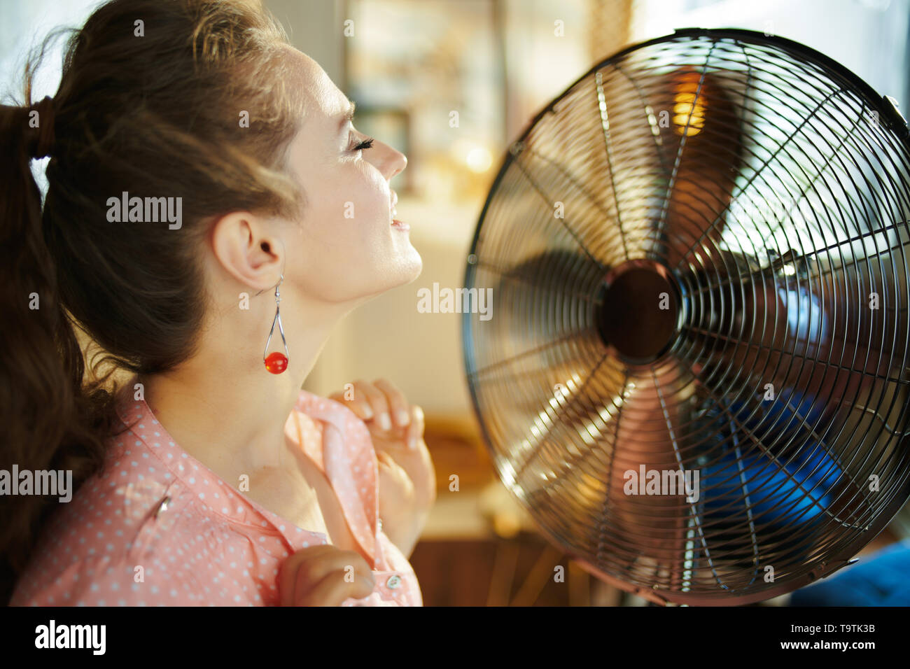 relaxed modern woman in the modern house in sunny hot summer day enjoying breeze in the front of working fan. - Stock Image