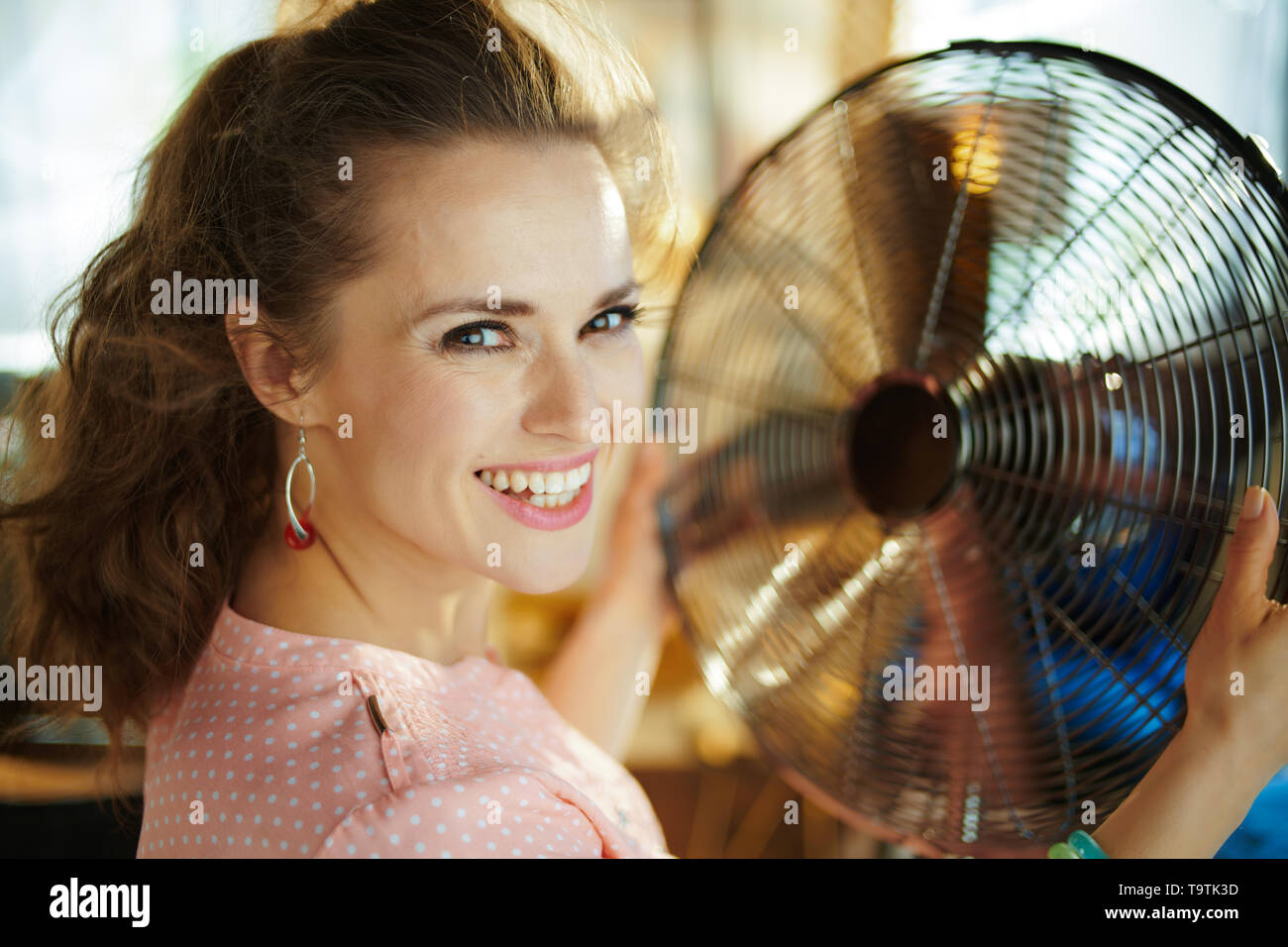 Portrait of smiling modern housewife in the modern living room in sunny hot summer day enjoying breeze air in the front of working fan. - Stock Image