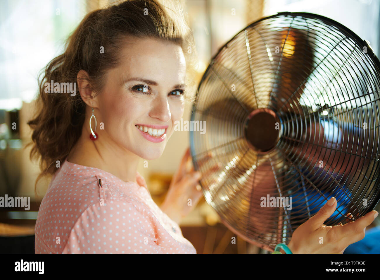 Portrait of happy stylish housewife in the modern house in sunny hot summer day enjoying freshness in the front of fan. - Stock Image