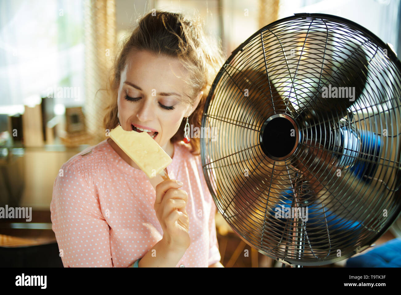 young housewife in the modern living room in sunny hot summer day using electric floor standing fan while eating ice cream. - Stock Image
