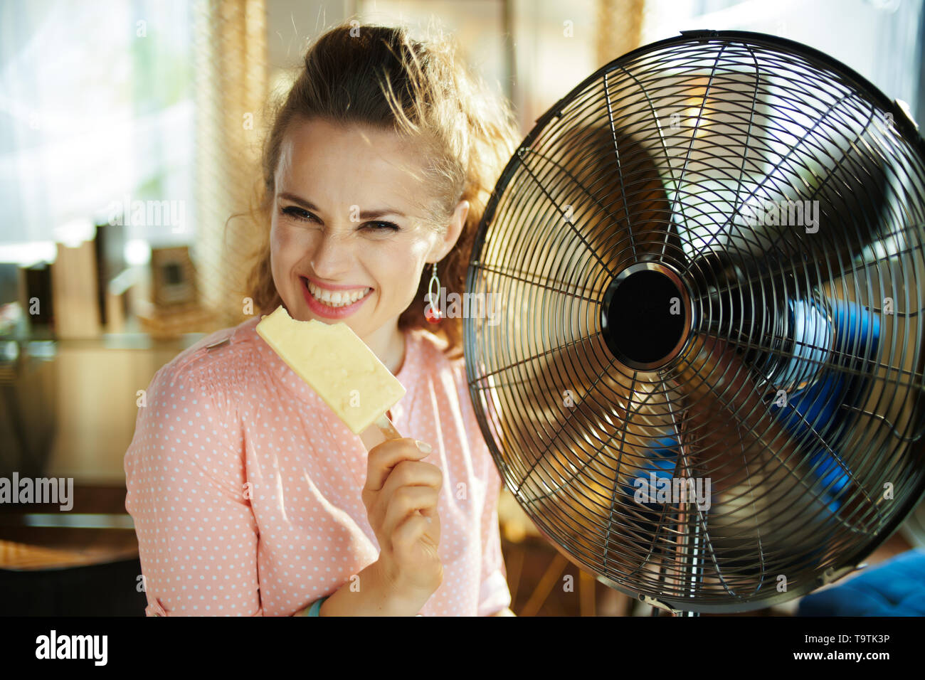 happy stylish woman with ice cream cooling down using electric metallic fan in the modern house in sunny hot summer day. - Stock Image