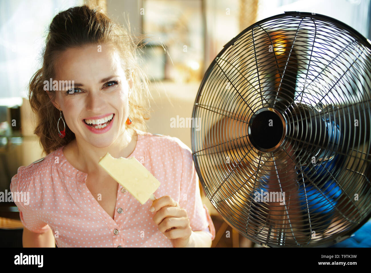 happy stylish woman with ice cream cooling down in the front of fan at modern home in sunny hot summer day. - Stock Image
