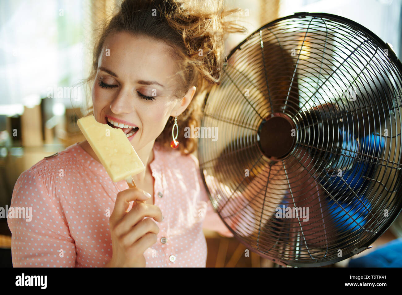happy stylish woman in the modern house in sunny hot summer day using electric metallic fan while eating ice cream. - Stock Image