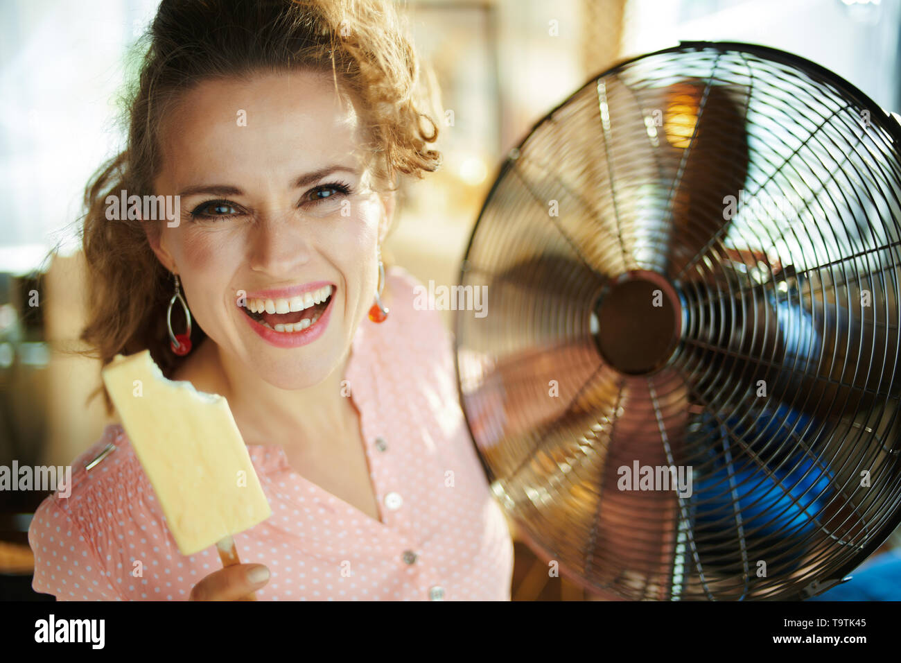 Portrait of smiling stylish woman with ice cream in the modern house in sunny hot summer day. - Stock Image