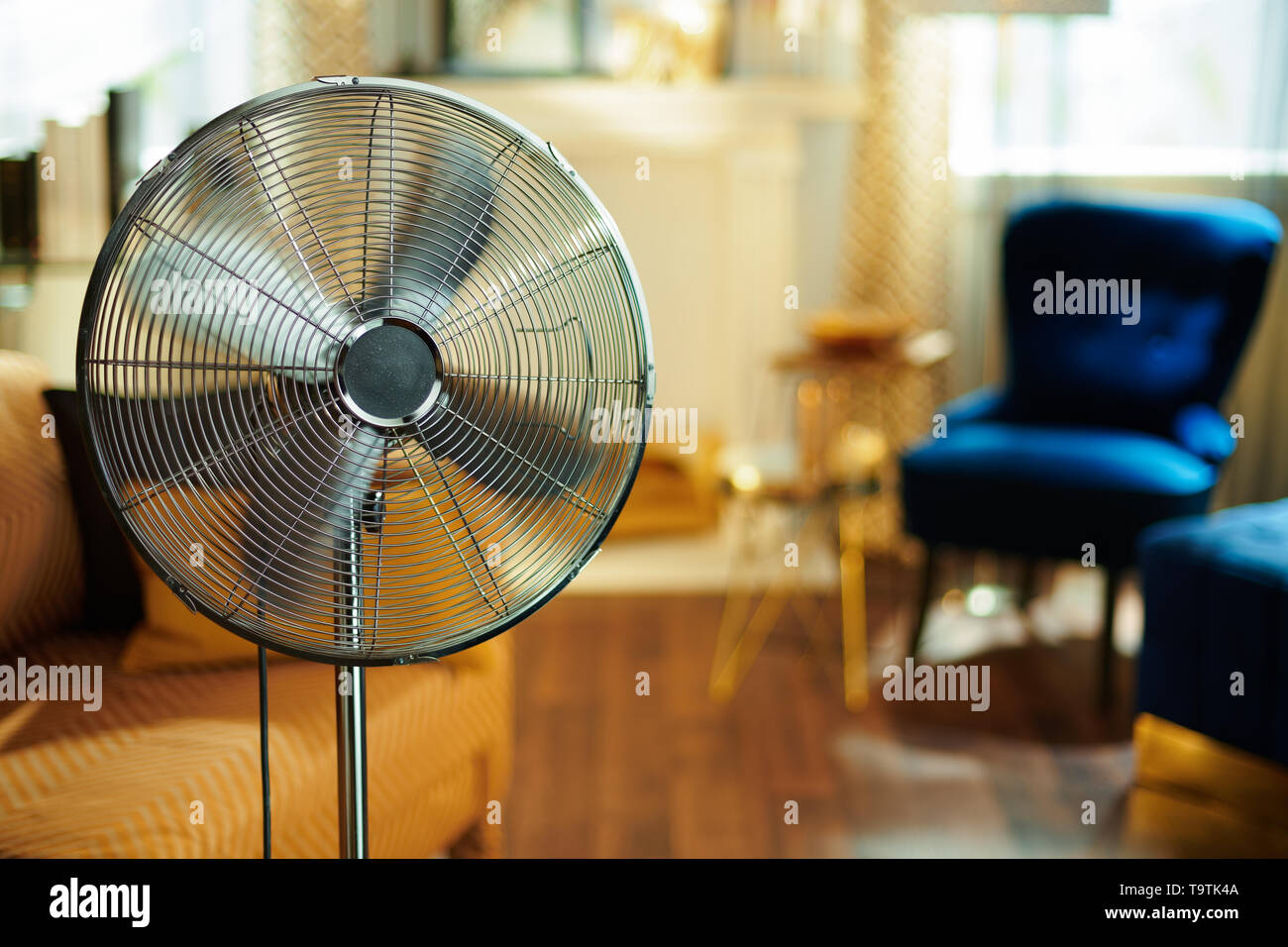 Closeup on working electric floor standing fan in the modern house in sunny hot summer day. - Stock Image