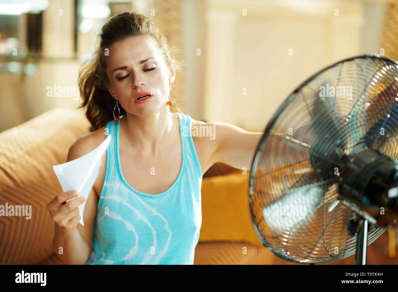 hot young woman in the modern house in sunny hot summer day in the front of working fan suffering from summer heat. - Stock Image