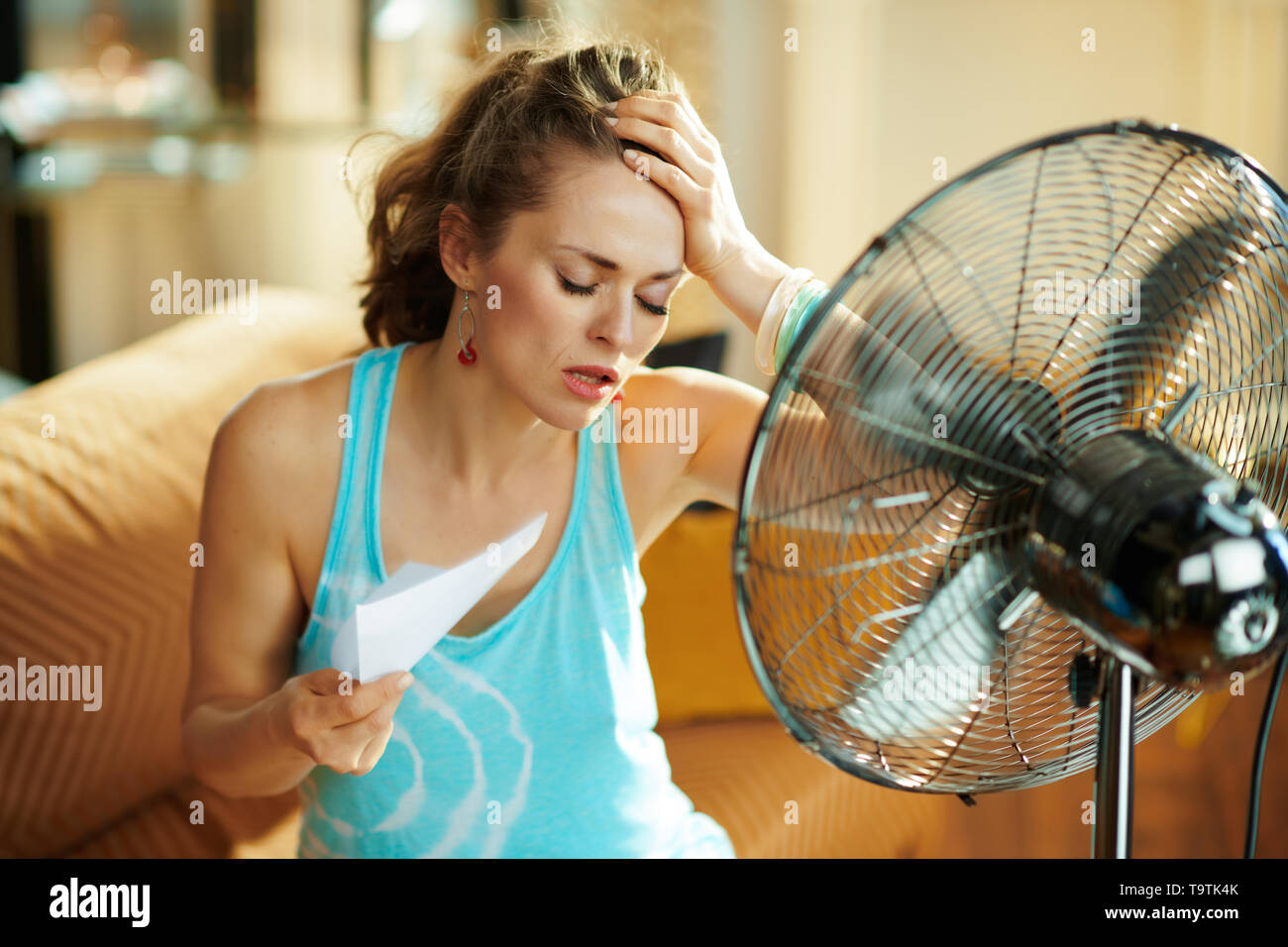 unhappy housewife in the modern house in sunny hot summer day in the front of working fan suffering from summer heat - Stock Image