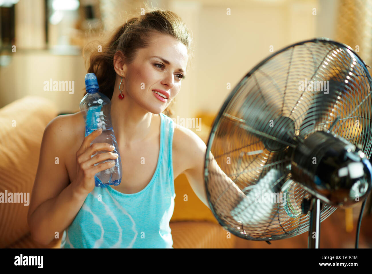 relaxed woman with bottle of cold water enjoying fresh air in the front of working fan at modern home in sunny hot summer day. Stock Photo