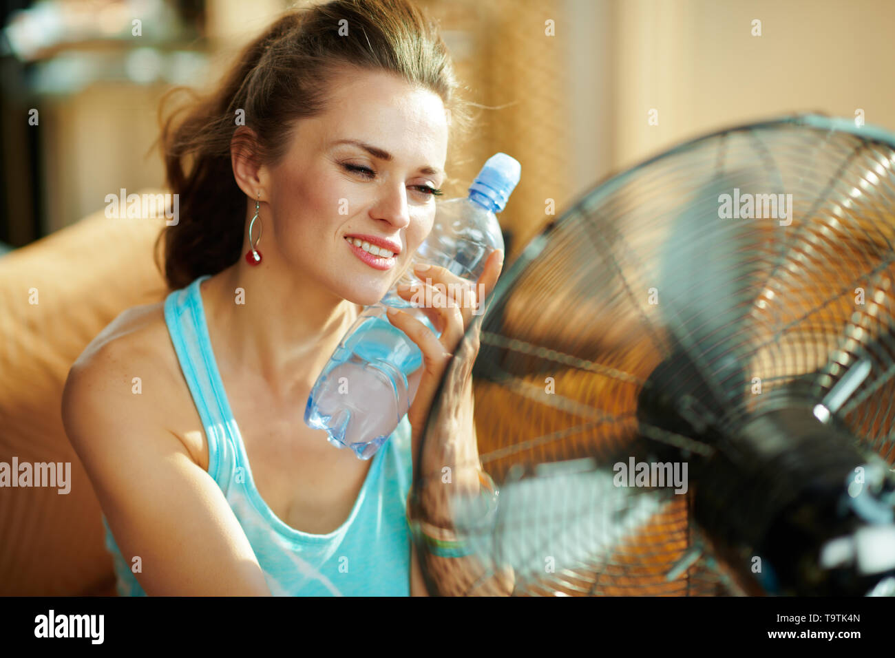 hot woman with bottle of cold water using electric metallic fan at modern home in sunny hot summer day. - Stock Image