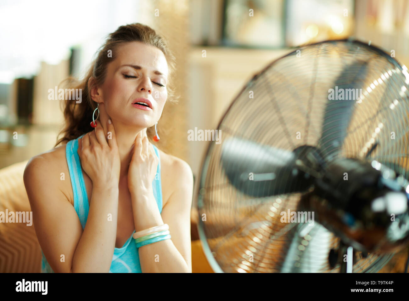 relaxed young woman in the modern living room in sunny hot summer day cooling down in the front of fan suffering from summer heat. - Stock Image