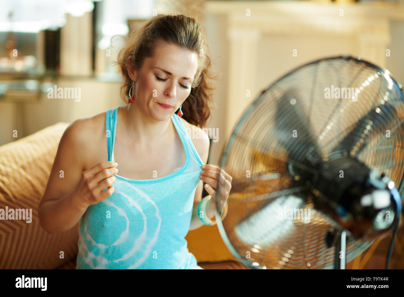 sweating woman at modern home in sunny hot summer day cooling down using electric floor standing fan suffering from summer heat. - Stock Image