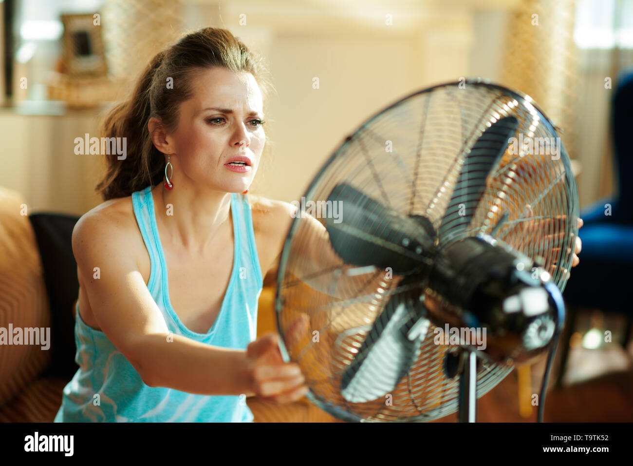 hot housewife in the modern living room in sunny hot summer day showing victory gesture suffering from summer heat. - Stock Image