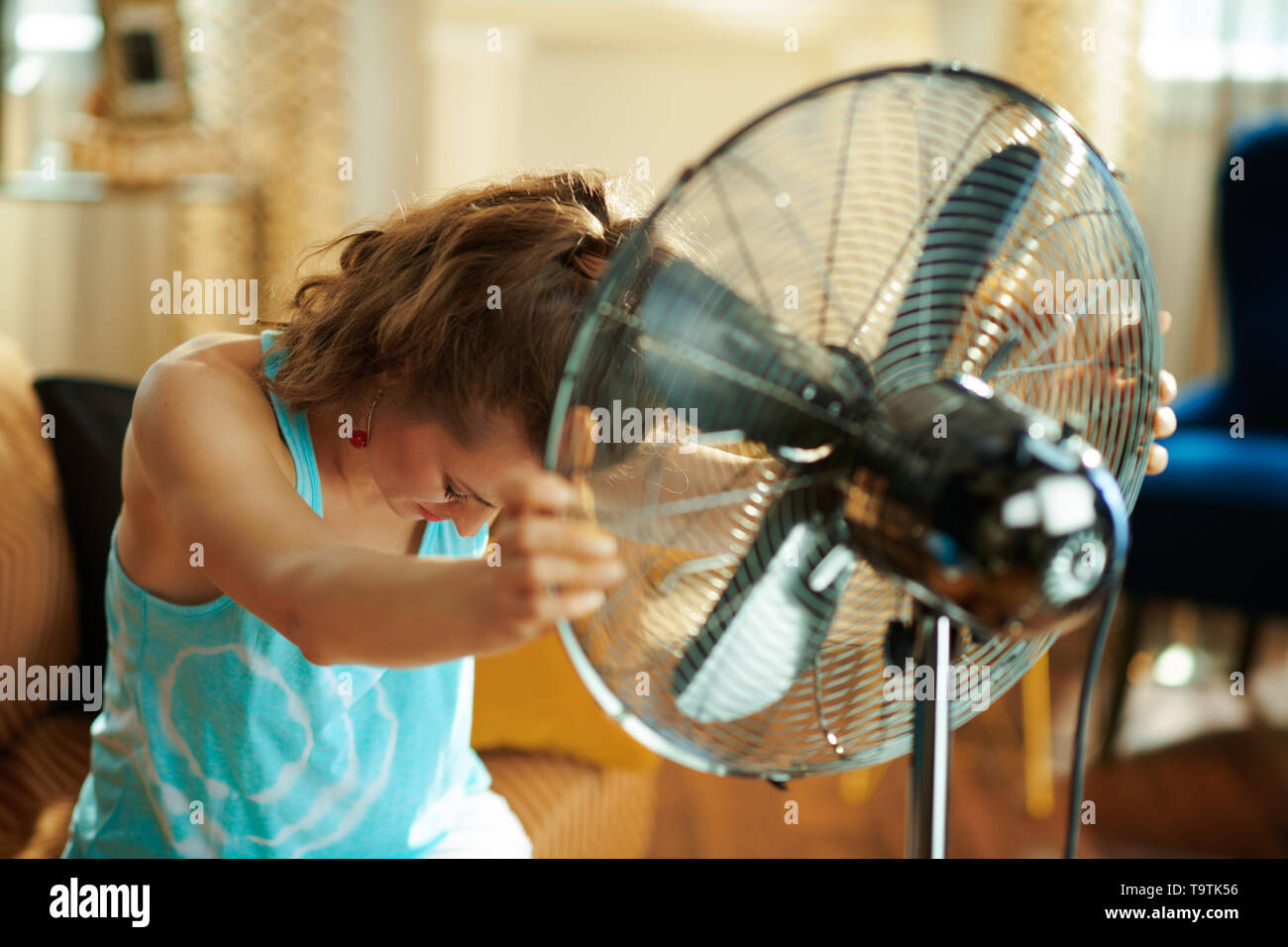 sad woman at modern home in sunny hot summer day showing victory gesture suffering from summer heat. - Stock Image