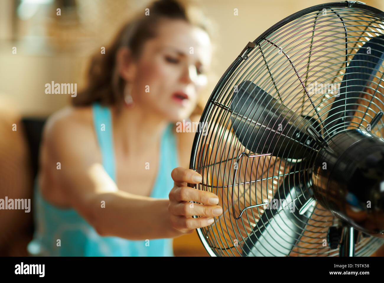Closeup on hot modern housewife in the modern living room in sunny hot summer day using electric metallic fan suffering from summer heat. - Stock Image