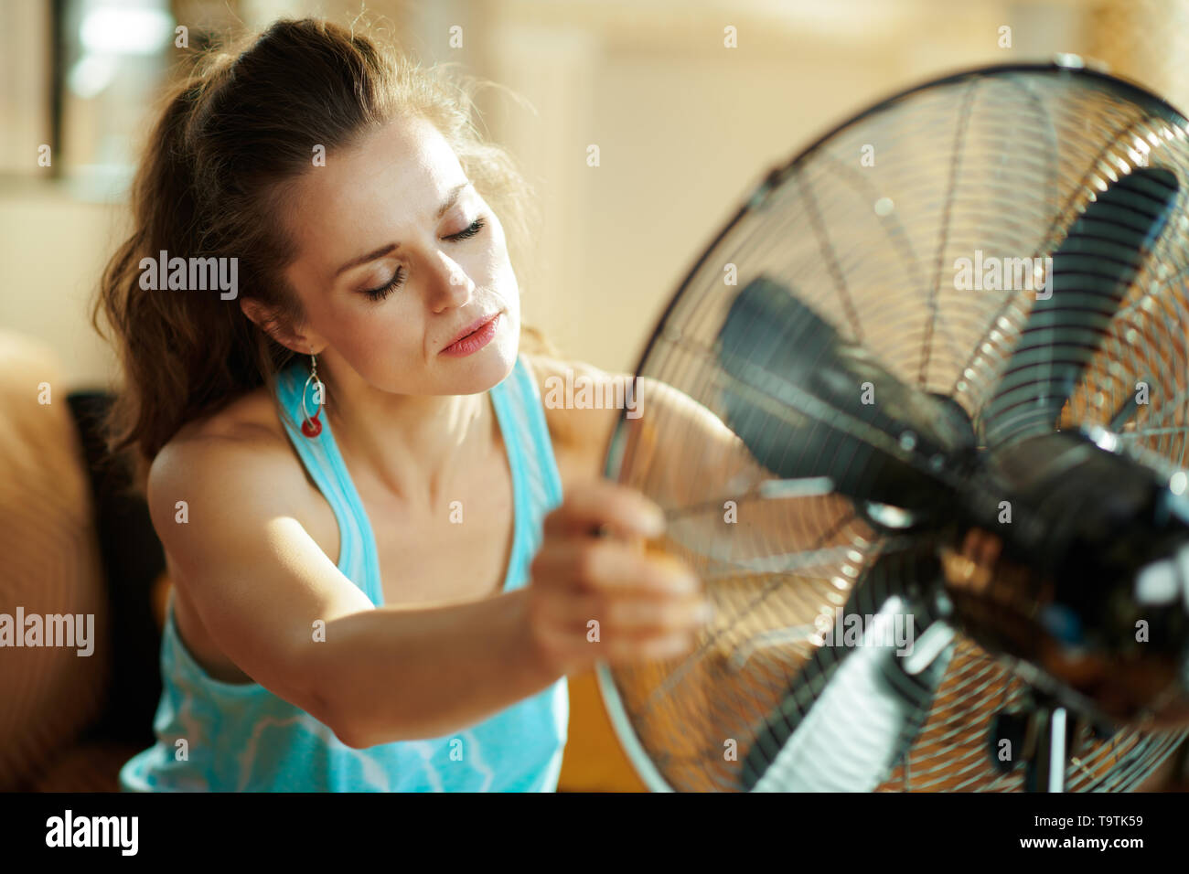 unhappy young housewife in the modern living room in sunny hot summer day enjoying freshness in the front of fan suffering from summer heat. - Stock Image