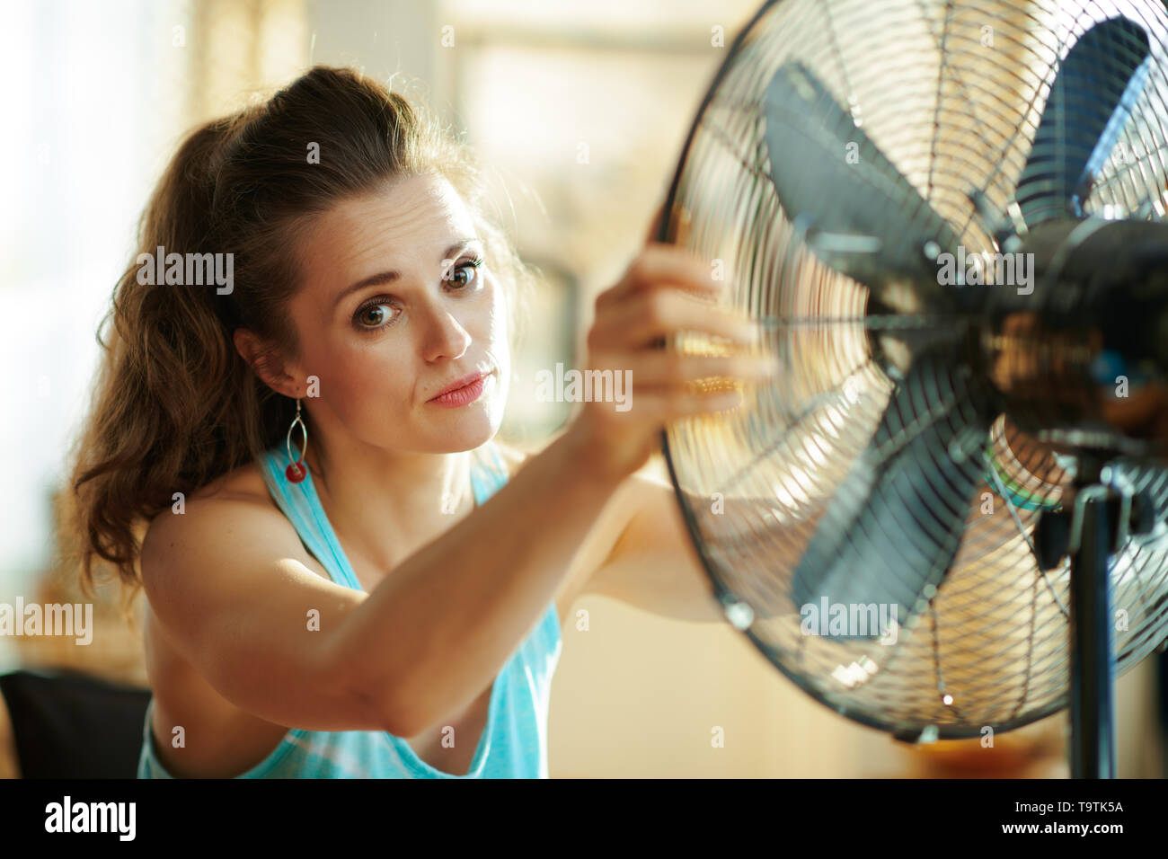 Portrait of woman in the modern living room in sunny hot summer day enjoying fresh air in the front of working fan suffering from summer heat. - Stock Image