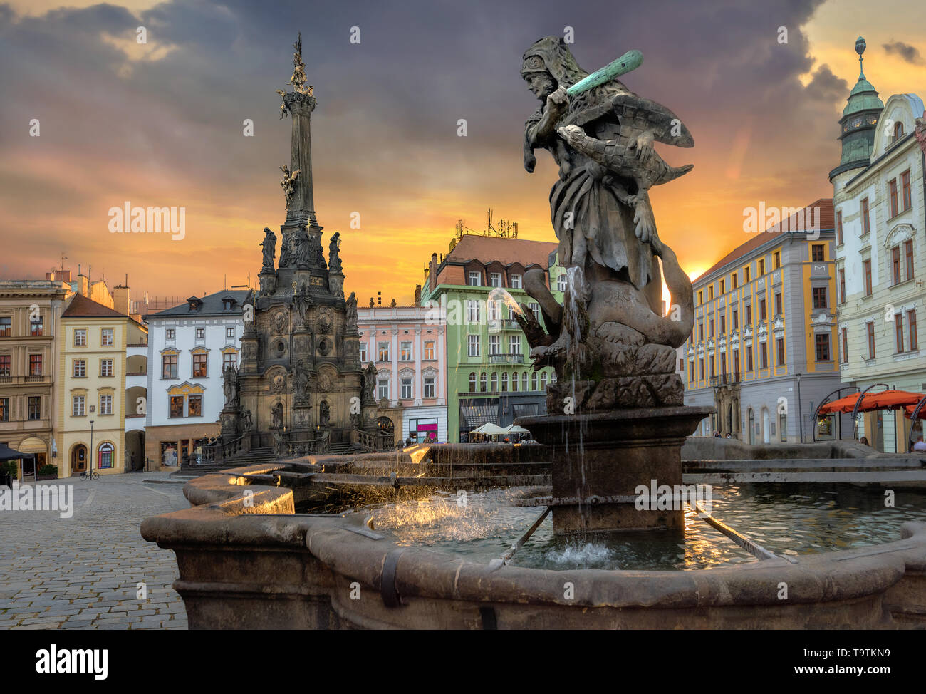Cityscape of main square with Hercules fountain and monument Holy Trinity Column at sunset sunlight. Olomouc, Czech Republic - Stock Image