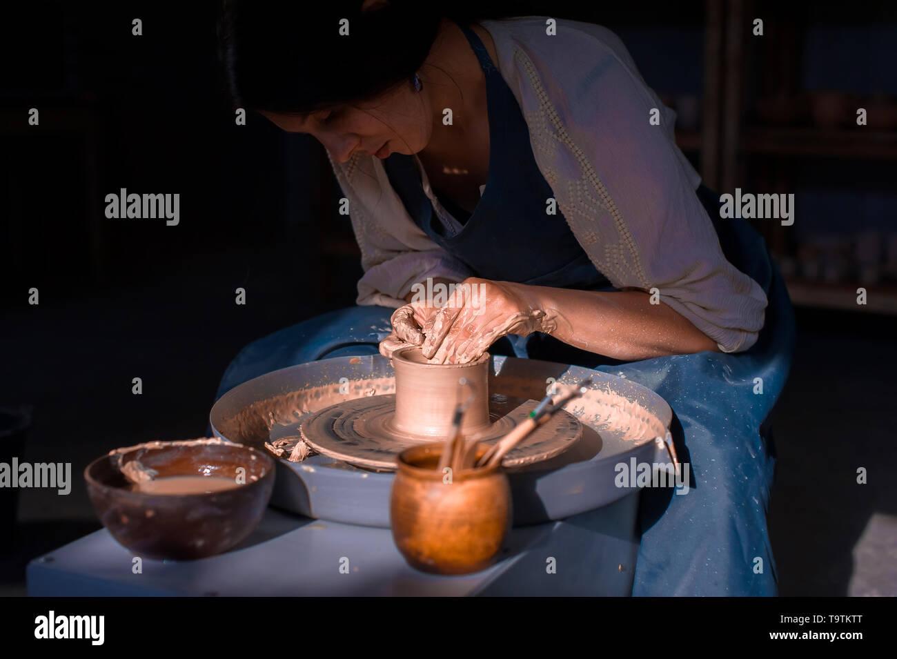Charming artisan master making ceramic pot on the pottery wheel . Hand work. - Stock Image