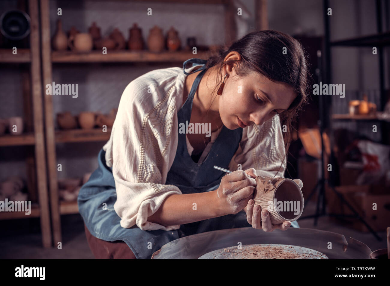 Stylish artisan working with pottery at the ceramic workshop. Handmade products. - Stock Image
