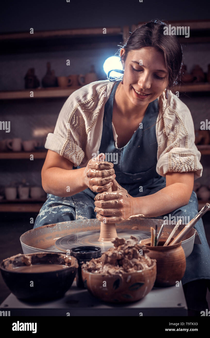 Charming artisan woman working with pottery at the ceramic workshop. Handcraft. - Stock Image