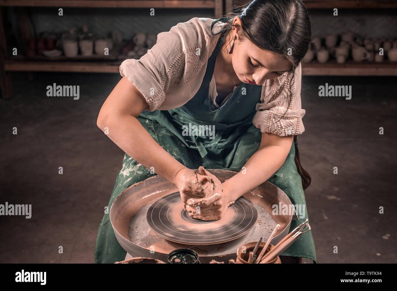 Stylish craftsman master making ceramic pot on the pottery wheel . Handmade. - Stock Image