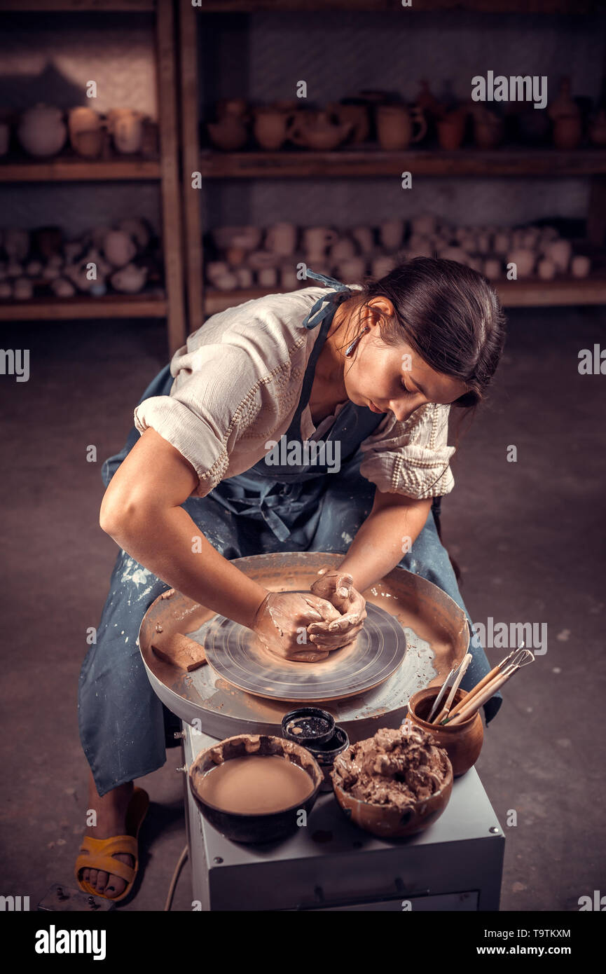 Charming potter female student shows how to work with clay and pottery wheel. Handwork. - Stock Image