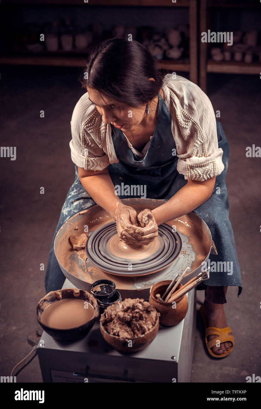 Charming artisan girl sculptor works with clay on a Potter's wheel and at the table with the tools. Handicraft industry. - Stock Image