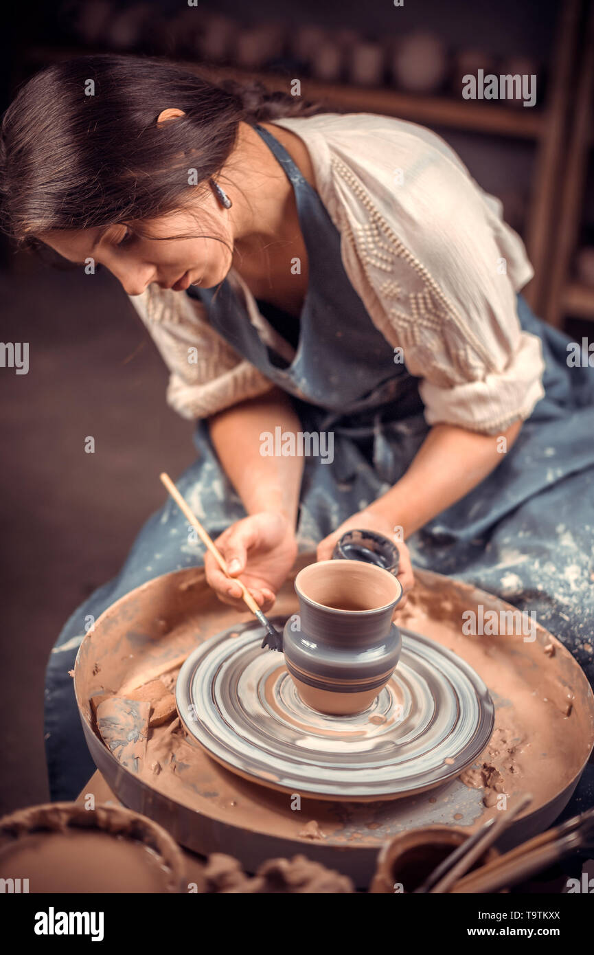 Charming young and cheerful woman demonstrates the process of making ceramic dishes using the old technology. Handmade products. - Stock Image
