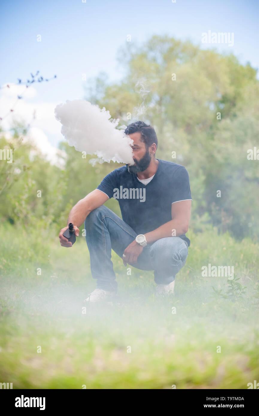 Stylish man exhales cloud of smoke. Handsome man. - Stock Image