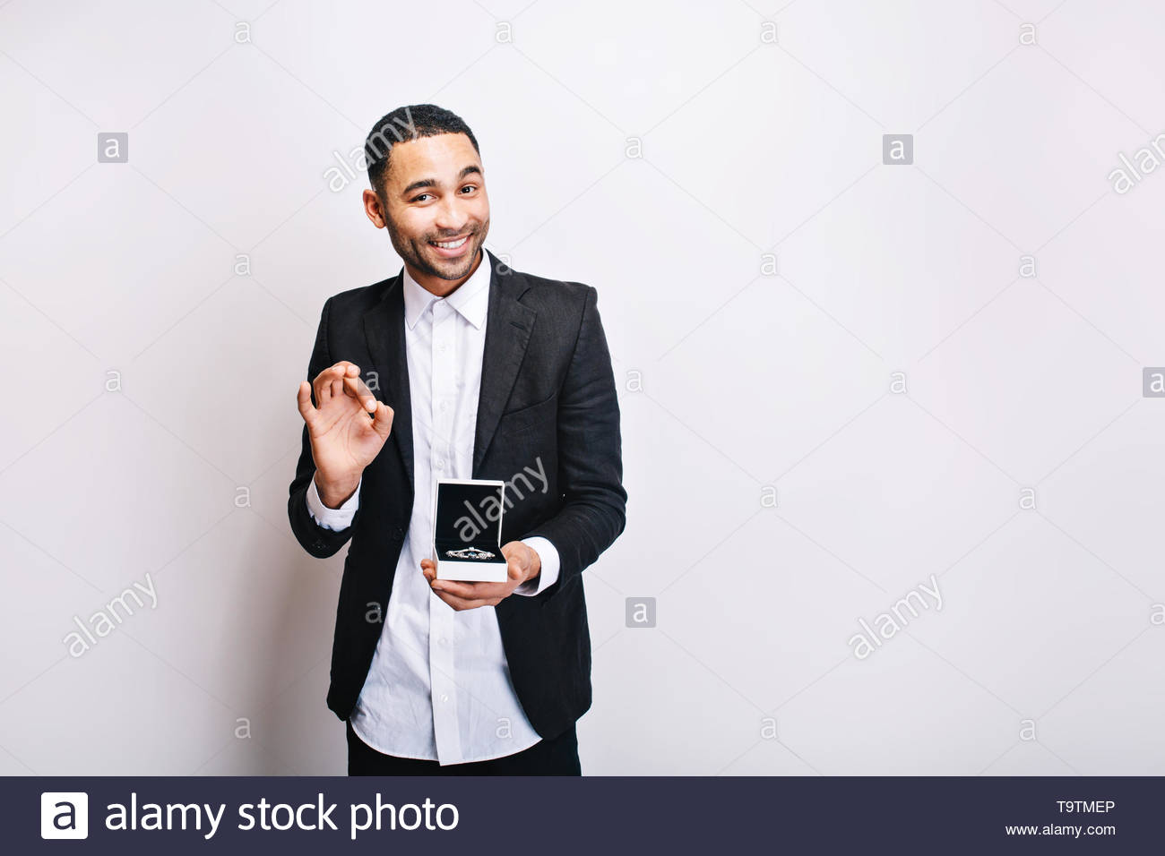 Happy handsome guy in luxury white shirt, black jacket holding gift and smiling to camera on white background. Holidays time, making surprise, ornamentation, cheerful mood - Stock Image