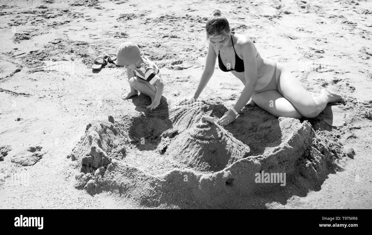 Black and white photo of young mother with her 3 years old child son sitting on the sandy sea beach, playing with toys and building sand castle - Stock Image