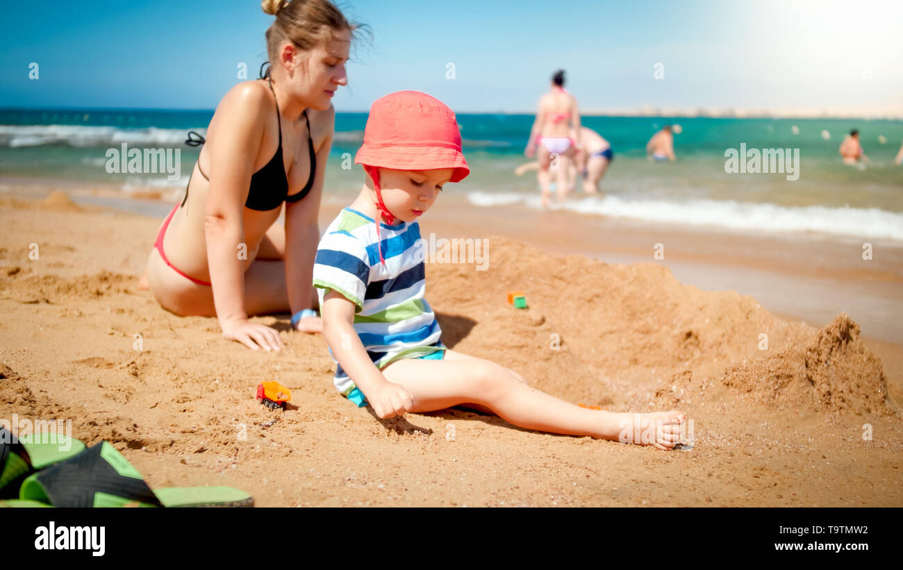 Photo of 3 years old toddler boy building sand castle with young mother the ocean beach. Family relaxing and having fun on the summer holiday vacation - Stock Image