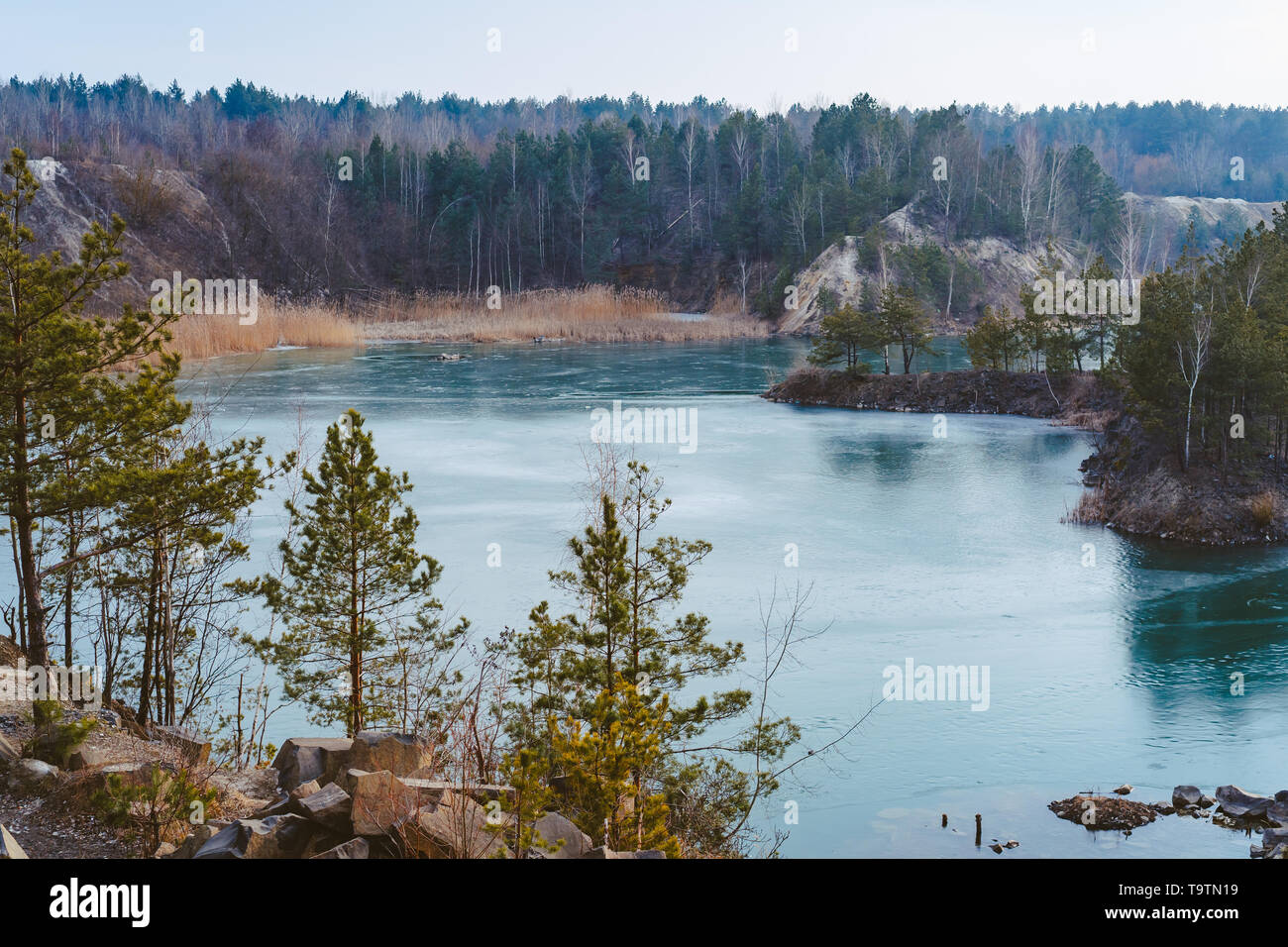 Beautiful quarry, the lake is covered with thin ice - Stock Image