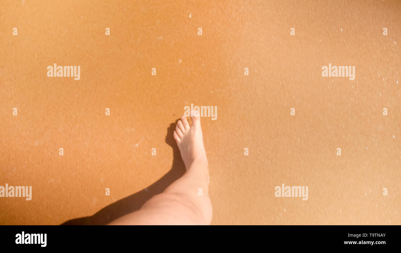 POV photo of male feet stepping wet sand at sea beach - Stock Image