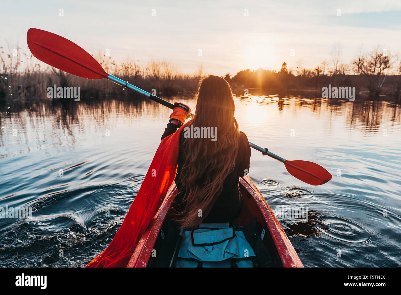 Back view of happy cute girl holding paddle in a kayak on the river - Stock Image