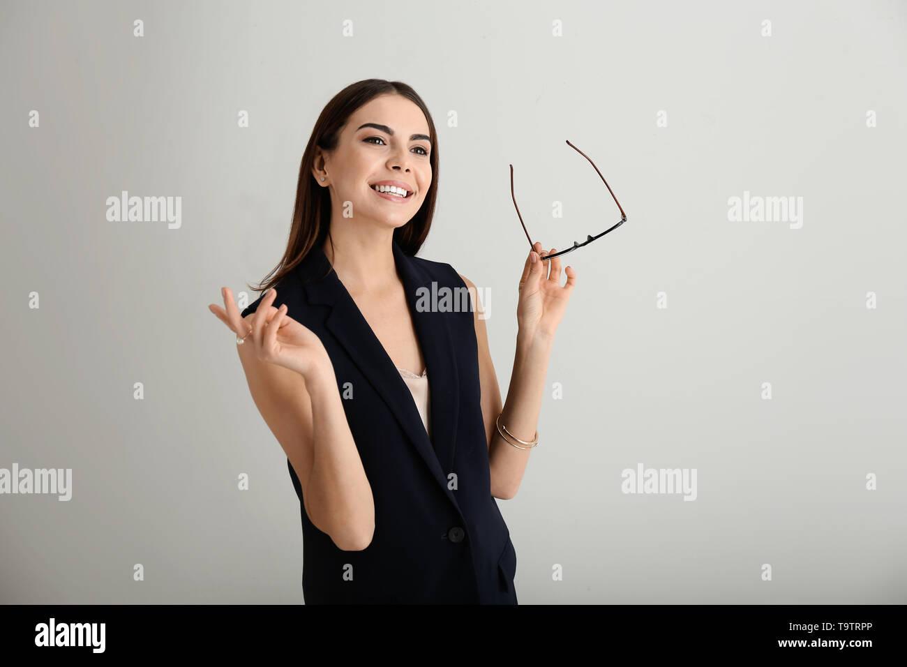 Portrait of beautiful businesswoman on light background - Stock Image
