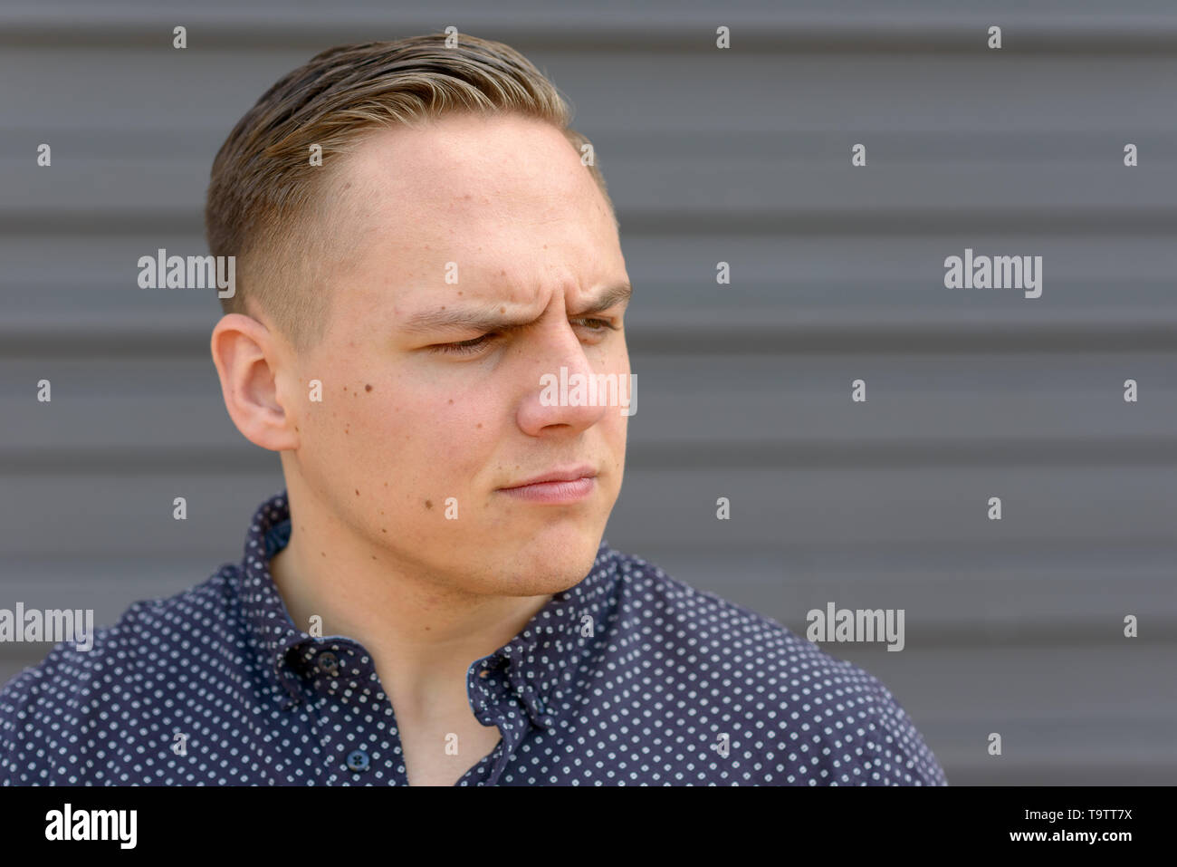 Close up of a Thoughtful stressed young man looking aside with a dubious expression - Stock Image