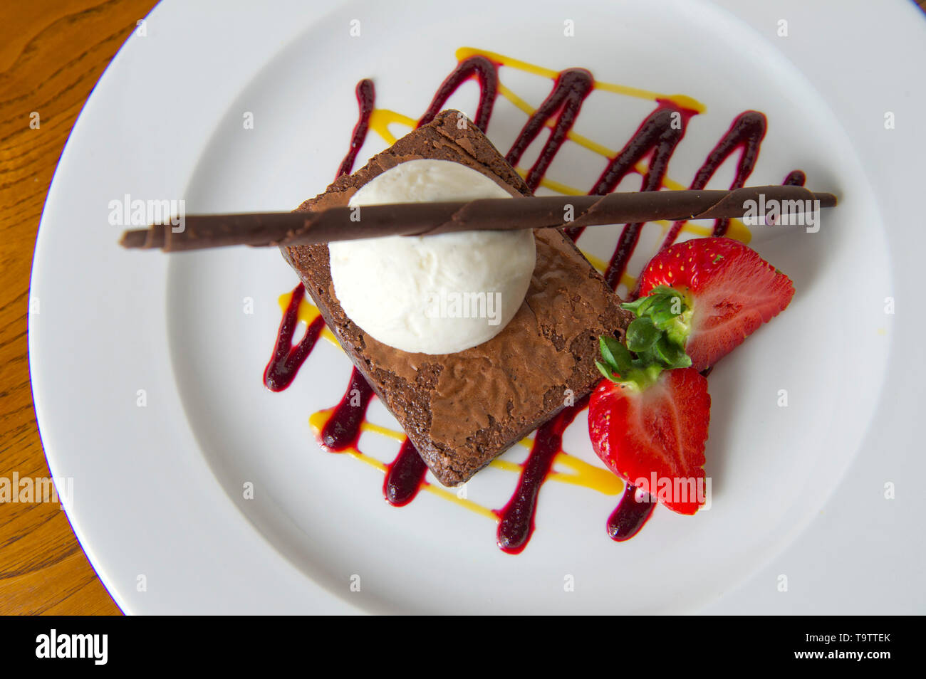 Chocolate  brownie with strawberries and ice-cream - Stock Image