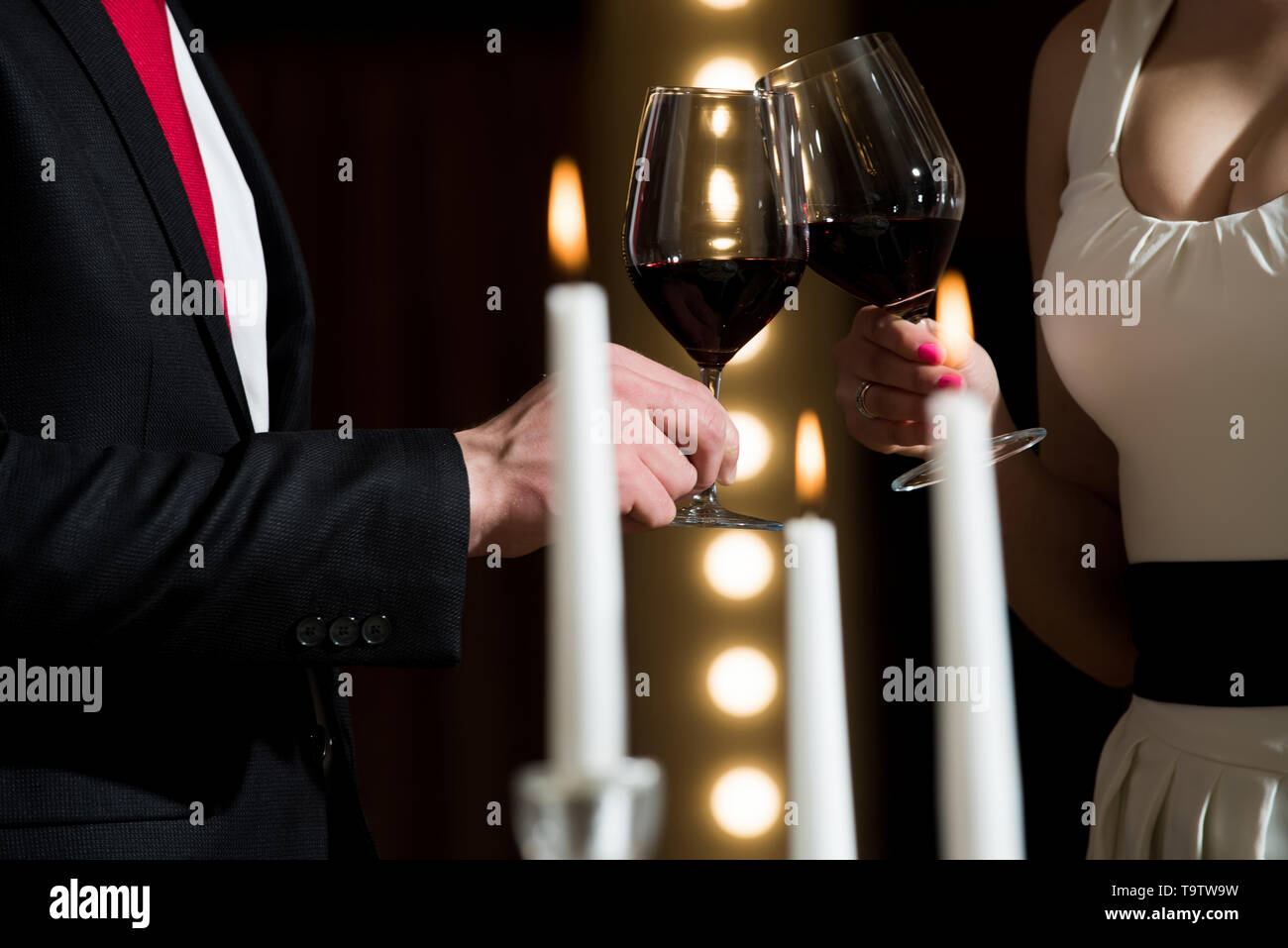 clink glasses with red wine of couple at meeting - Stock Image