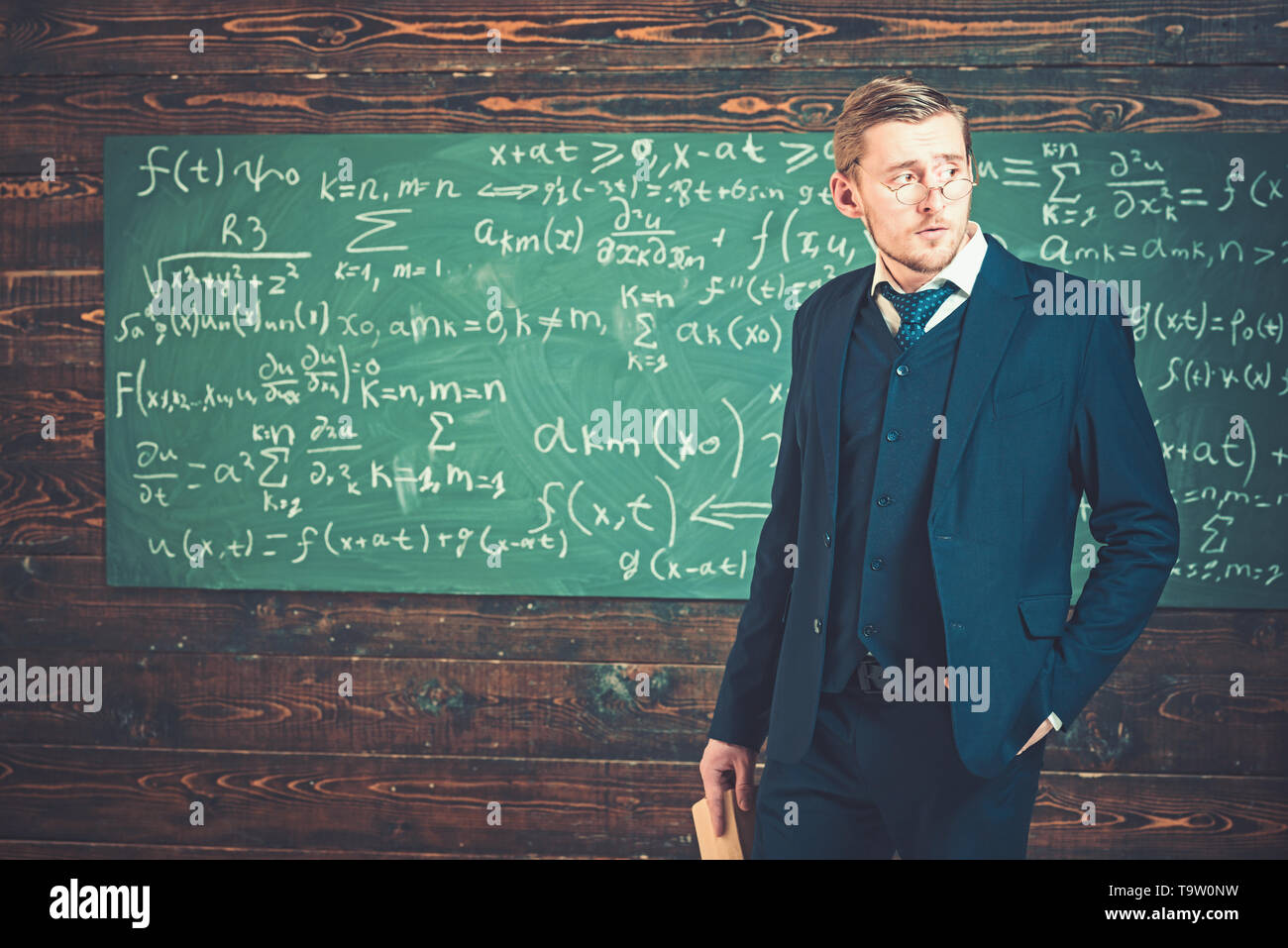 Young aristocrat in glasses holding book and posing in classroom. Elite education concept - Stock Image