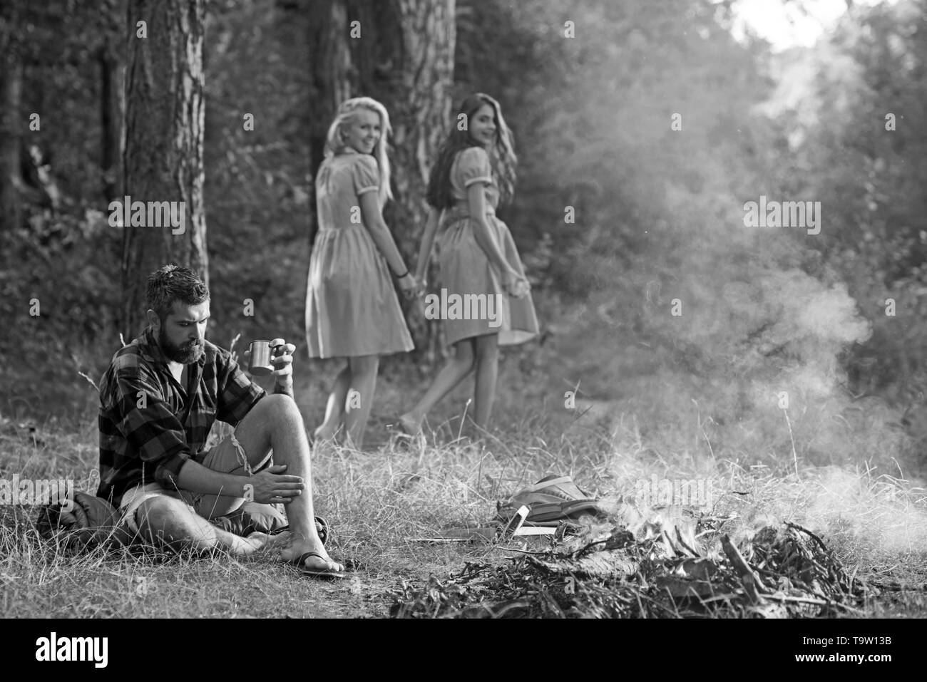 Two happy smiling girls looking back at thoughtful man sitting on grass. Bearded man in lumberjack shirt thinking while looking at flames of campfire - Stock Image
