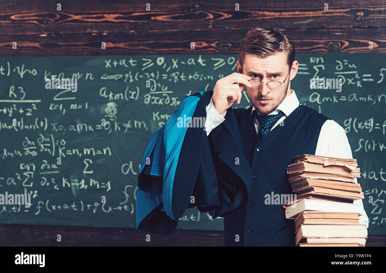 Young professor holding pile of books looking over his glasses. Aristocrat scholar in elite college - Stock Image